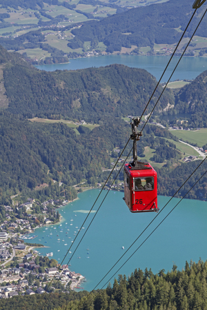 The hike or cable car ride to the 1522 m high Zwölferhorn gives us a wonderful view of Sankt Gilgen and lakes Wolfgangsee and Mondsee in the Salzkammergut. Stock Photo