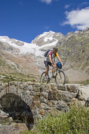 Mountain bike ride over an old stone bridge in Val Veny on the southern slopes of Mont Blanc Massif