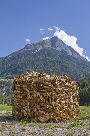 Firewood provided in oversized metal baskets waiting in front of the mountain forest on the removal