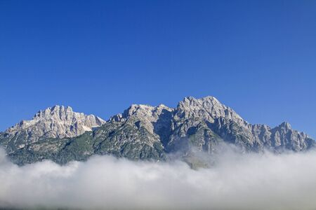 The craggy peaks of the Loferer Steinberge rise above the swath of the morning mist