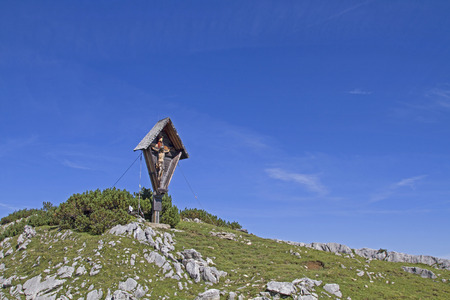 The summit cross on the Satteljoch  in the Karwendel mountain range, a popular hut mountain north of the Plumsjoch hut Standard-Bild - 117879543