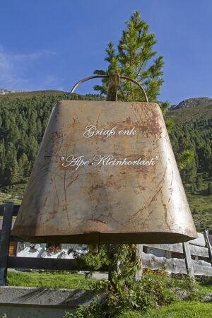 An oversized cowbell welcomes mountain hikers in the Horlach valley and invites them to a stop in the rustic alpine hut