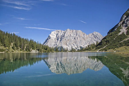 The idyllic Seeebensee in the Mieminger mountains in front of the mighty backdrop of the Zugspitze is a popular hiking destination for many climbers Standard-Bild - 118665330
