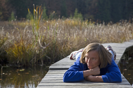 Woman relaxes on one of the last autumn days and lies on the landing stage of a small moor lake Standard-Bild