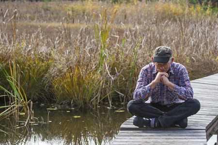Man sits meditating on the boat dock in the middle of a reed-covered moor lake
