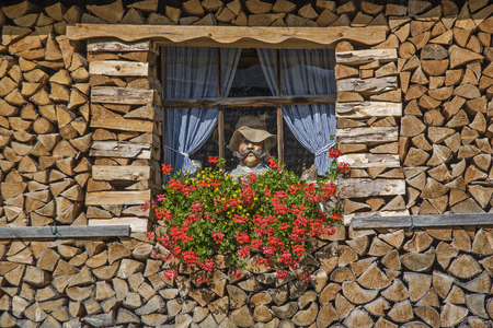 Alps idyll or kitsch - window with wooden figure at a Bavarian wooden hut