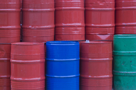 Many colorful metal bins filled with various machine oils are piled up in the yard of the industrial site Stock Photo - 122173961