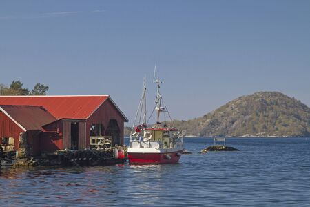Boat huts and fishing boats in Bjornevag an idyllic quiet fishing village on Spindsfjorden