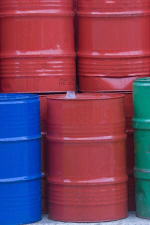 Many colorful metal bins filled with various machine oils are piled up in the yard of the industrial site