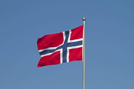 Norwegian flag fluttering in the wind against a blue cloudless sky