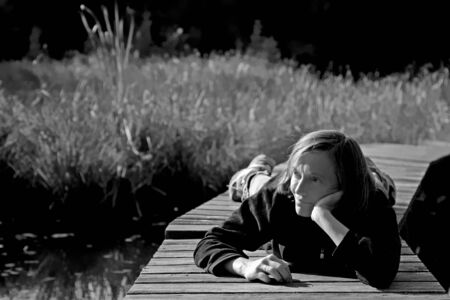 Woman relaxes on one of the last autumn days and lies on the landing stage of a small moor lake