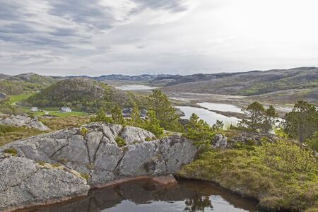 Low tide prevails at the fjord at Tjoernsey and Vikna and leaves behind small salt lakes and ponds