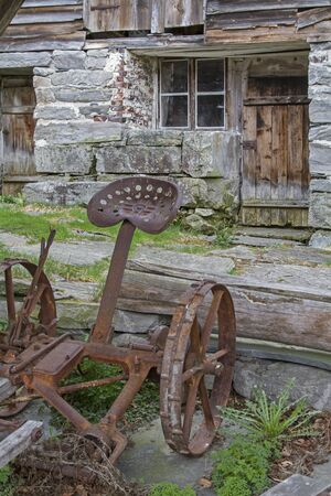 Rusted old plow stands in the garden of an abandoned norwegian farmhouse