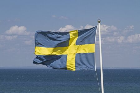 Swedish flag flutters in the wind in front of blue cloud sky Stockfoto