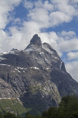 The mighty Romsdalshorn, with its bold silhouette, dominates the scenic Rauma Valley in Norway with the Trolll wall opposite Banco de Imagens