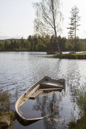 Shipwreck - old forgotten wooden boat on a Norwegian lake was full of water