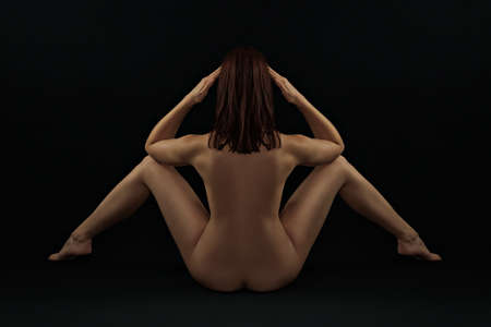 Erotic rear view - classic covert nude against a black background