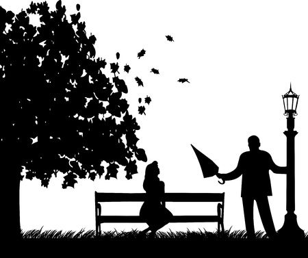 Un hombre joven con un paraguas, de pie cerca de una lámpara de la calle y conquistar a la chica de silueta