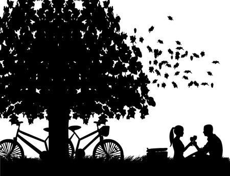 Pareja romántica en picnic, con las bicis en el parque bajo el árbol de pan tostado con una copa de vino en el otoño o el otoño silueta