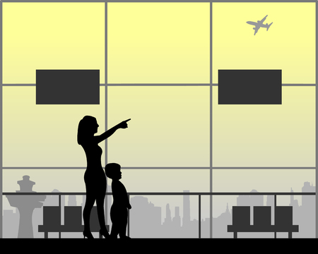 Mother shows the boy the plane flying at the airport