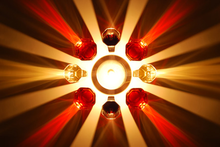 evocative: colored shadows of wine glass illuminated by a candle