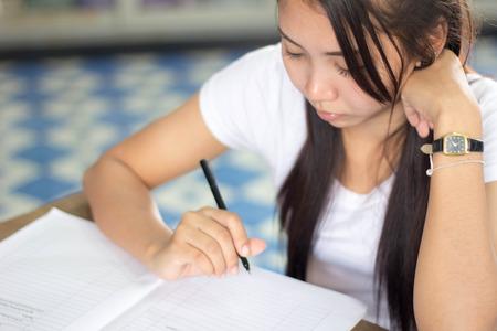 A thai woman wearing white shirt writing photo
