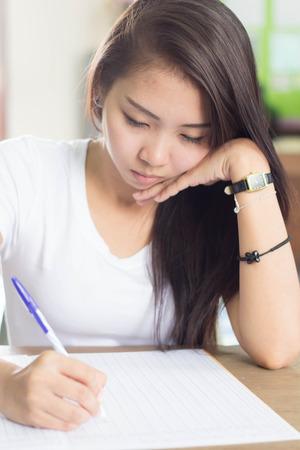 A woman wearing white t-shirt writing. photo
