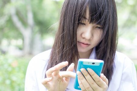 Portrait of thai student teen beautiful girl using her smart phone sitting in park. photo