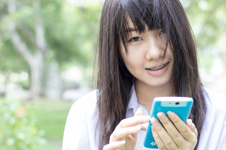 thai student: Portrait of thai student teen beautiful girl using her smart phone sitting in park. Stock Photo