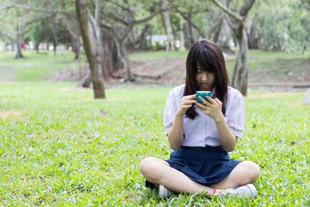 Portrait of thai student teen beautiful girl using her tablet sitting in park. photo