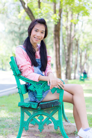 thai student: Portrait of thai student teen beautiful girl pink shirt Denim Shorts happy and relax On Park Stock Photo