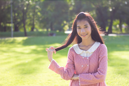 thai student: Portrait of thai student teen beautiful girl Dress Pink smile give heart and relax On Park
