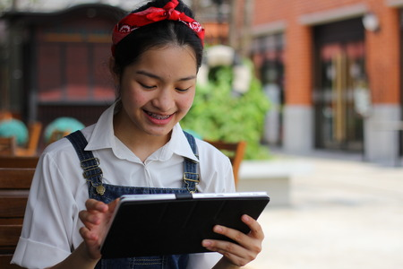 thai student: Portrait of thai student teen beautiful girl using her tablet. Stock Photo