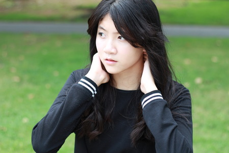 thai student: Portrait of thai student teen beautiful girl Black Dresses relax in park.
