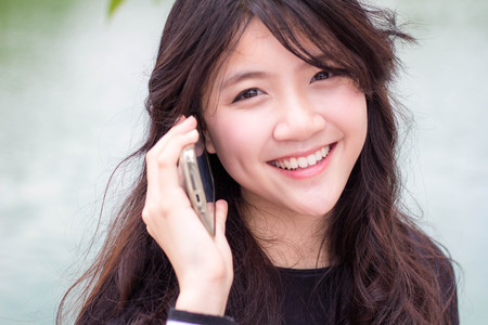 answer phone: Portrait of thai student teen beautiful girl Answer the phone and smile.