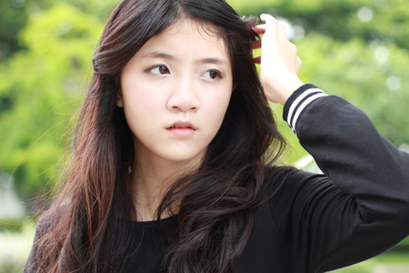 asian style: Portrait of thai student teen beautiful girl Black Dresses relax in park.