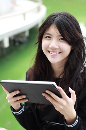 thai student: Portrait of thai student teen beautiful girl using her tablet sitting in park.