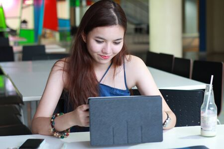 android tablet: Portrait of thai adult beautiful girl using her tablet and smile in university.