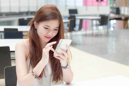 very: very happy thai adult beautiful girl read message on Smartphone.