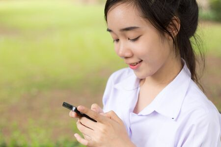 thai student: Portrait of thai student teen beautiful girl using her phone and smile.