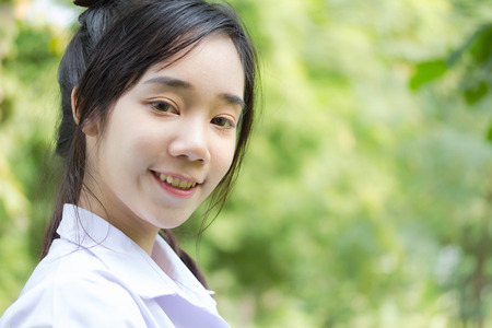 teens: Portrait of thai student teen beautiful girl relax and smile in park.