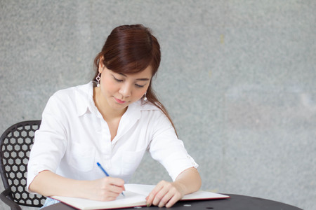 writing paper: Portrait of thai adult businesswoman beautiful girl write a book. Stock Photo