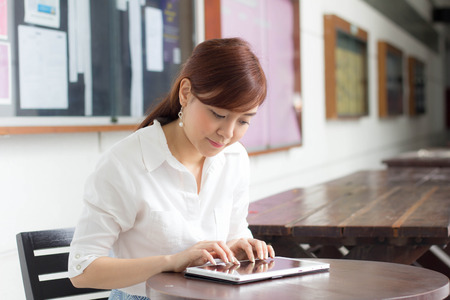 thai: Portrait of thai adult businesswoman beautiful girl typing tablet. Stock Photo
