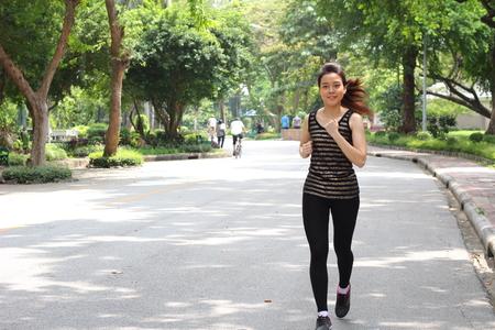 exert: Portrait of thai adult beautiful girl doing running exercises in the park Stock Photo