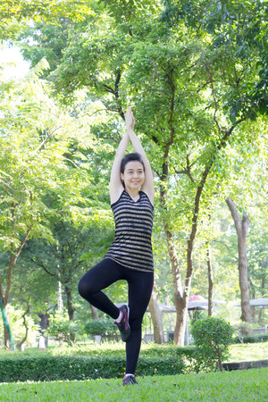 exert: Portrait of thai adult beautiful girl doing yoga exercises in the park