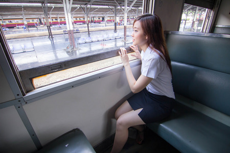 thai student: Portrait of thai student university beautiful girl relax and smile, Leisure travel by rail Stock Photo