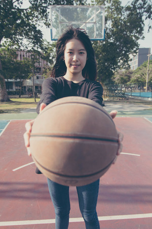 asia thai teenager Women black T-Shirt relax and smile in Basketball court Stock Photo