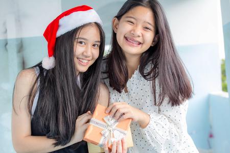 dar un regalo: dos adolescente asiático tailandés hermosa niña feliz año nuevo y dar un regalo Amigos