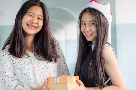 dar un regalo: two asia thai teen beautiful girl happy new year and Give a Gift Friends
