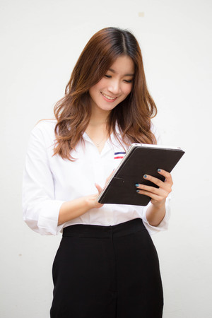 Portrait of thai adult working women white shirt using her tablet. Stock Photo